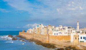 Blick auf die Sqala de Ville und die dahinter liegende Medina von Essaouira an der Atlantikküste Marokkos. Das Meer schlägt leichte Wellen, der Himmel ist etwas bewölkt, die Gebäude der Altstadt leuchten in kräftigen Farben, vor allem in blau und weiss.