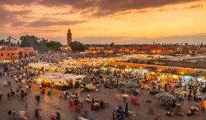 lebhaftes Treiben auf dem grossen Platz Djemaa el Fna in Marrakech in der Abenddämmerung. Die Verkaufsstände sind beleuchtet, der Himmel ist gefärbt in gelb, orange und violett. Links hinten ist die Koutoubia-Moschee zu sehen, umgeben von Palmen.